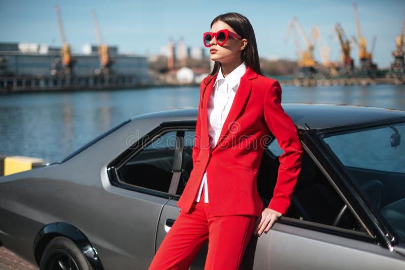 Forme a la muchacha que se coloca al lado de un coche deportivo retro en el sol Mujer elegante en un traje rojo y las gafas de so foto de archivo