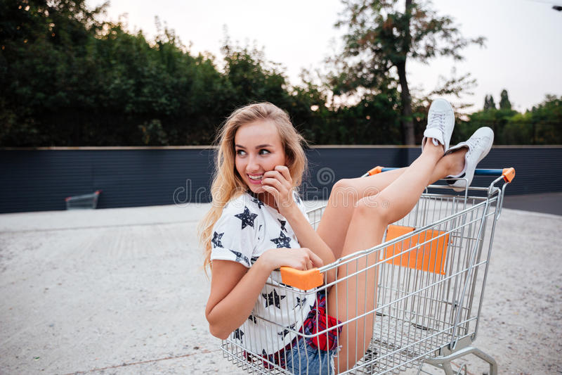 Forme a la muchacha que se divierte que se sienta en carro de la carretilla de las compras al aire libre imagen de archivo