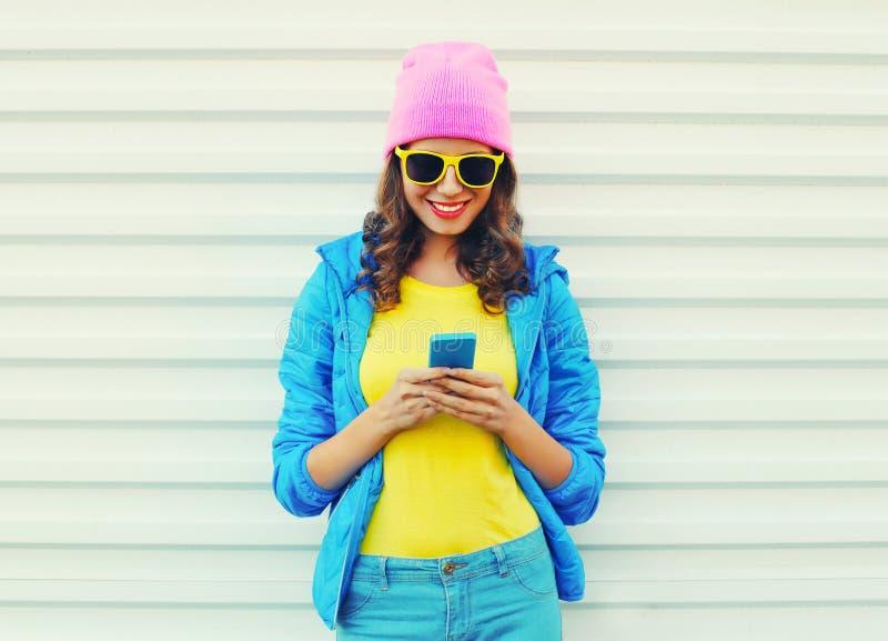 Forme a la muchacha sonriente fresca feliz que usa smartphone en ropa colorida sobre el fondo blanco que lleva las gafas de sol r imagen de archivo libre de regalías
