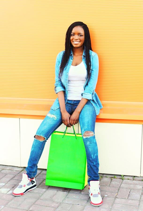 Forme a la mujer africana sonriente de los jóvenes con los panieres en ciudad sobre fondo anaranjado imagen de archivo