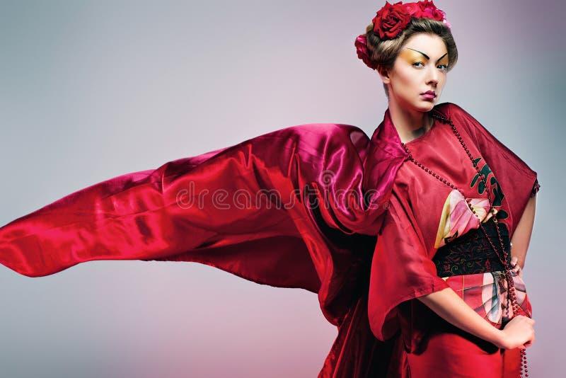 Forme a la mujer asiática que lleva el kimono rojo japonés tradicional. Gei foto de archivo