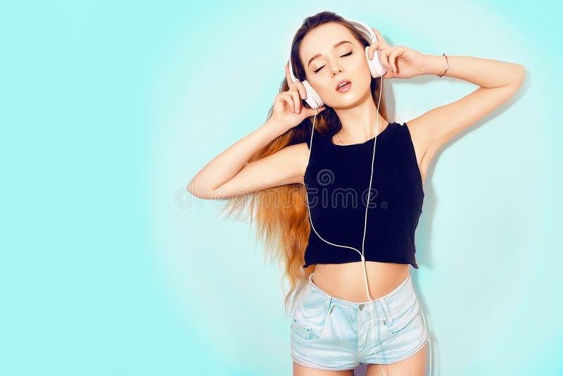 Forme a la mujer bastante fresca en auriculares que escucha la música sobre fondo azul Adolescente joven hermoso con el pelo larg imagenes de archivo