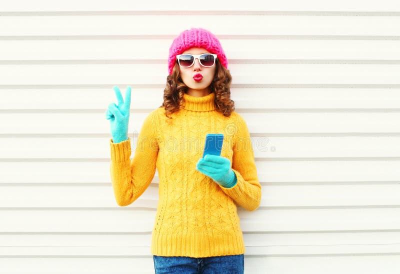 Forme a la mujer bastante joven con el smartphone que lleva la ropa hecha punto colorida sobre blanco fotografía de archivo