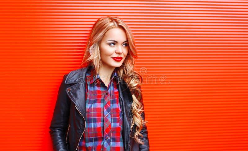 Forme a la mujer bastante rubia del retrato que lleva estilo negro de la roca sobre rojo colorido imagen de archivo