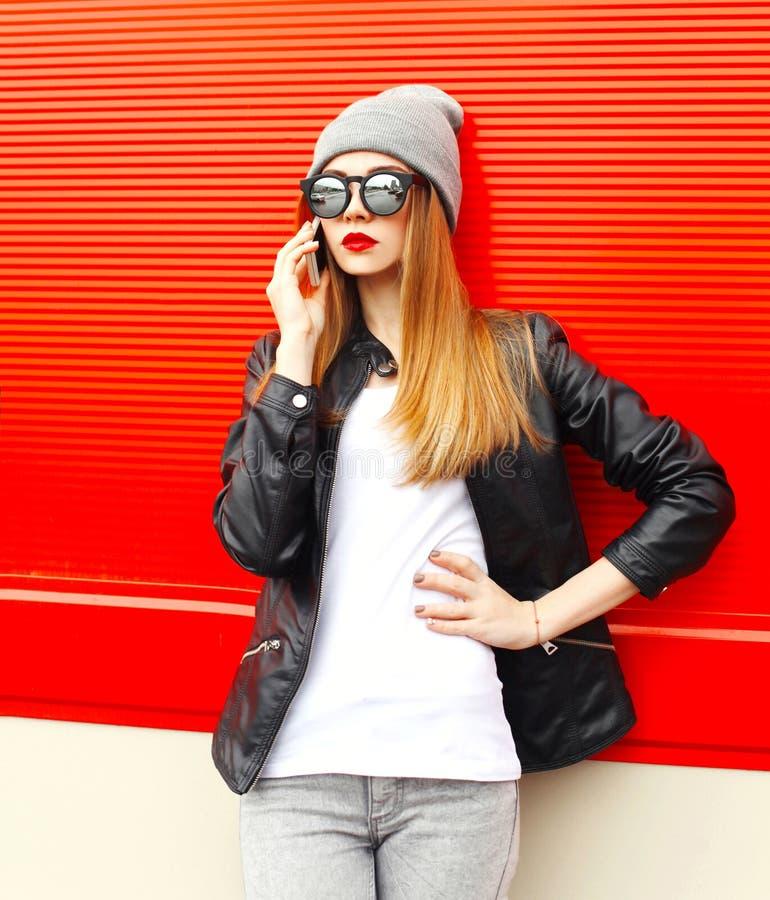 Forme a la mujer bonita que habla en smartphone en ciudad sobre rojo imagen de archivo libre de regalías