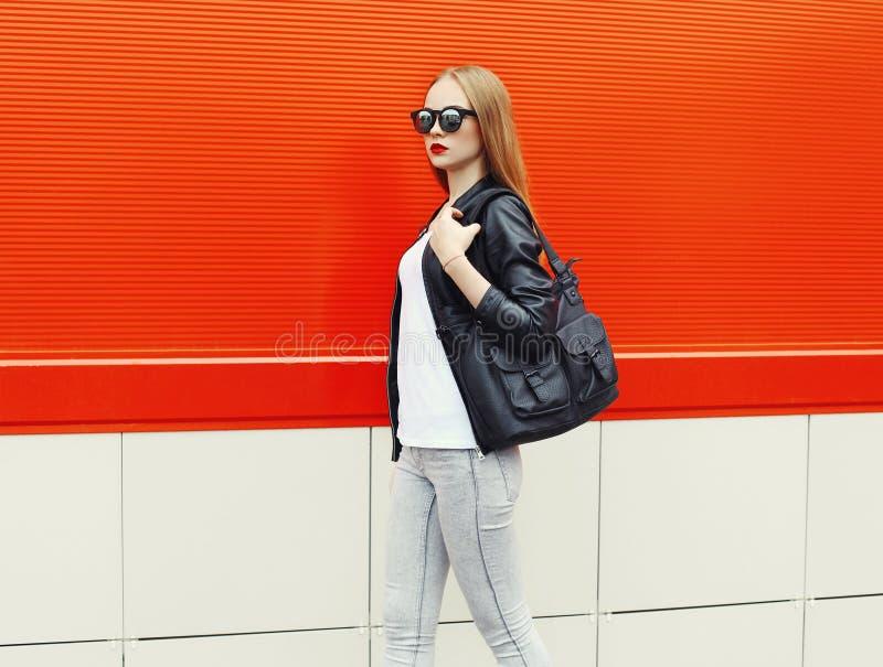 Forme a la mujer bonita que lleva un negro de la roca la chaqueta de cuero, las gafas de sol y bolso en perfil fotos de archivo libres de regalías