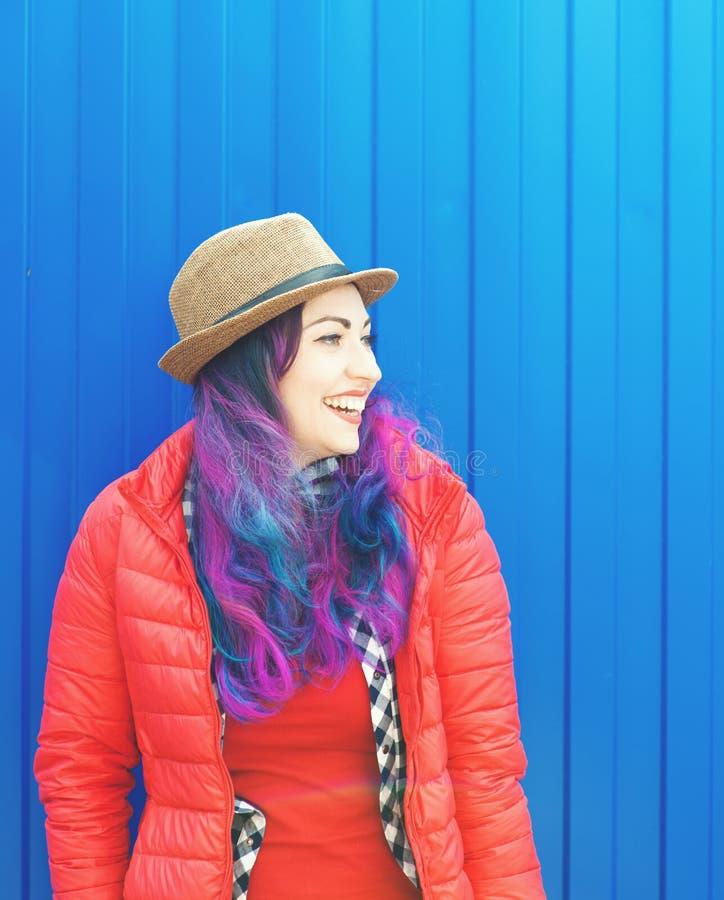 Forme a la mujer del inconformista con el pelo colorido que se divierte foto de archivo