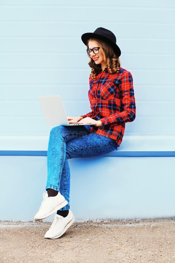 Forme a la mujer joven que trabaja usando el ordenador portátil en la ciudad, llevando la camisa a cuadros roja del sombrero negr imagenes de archivo