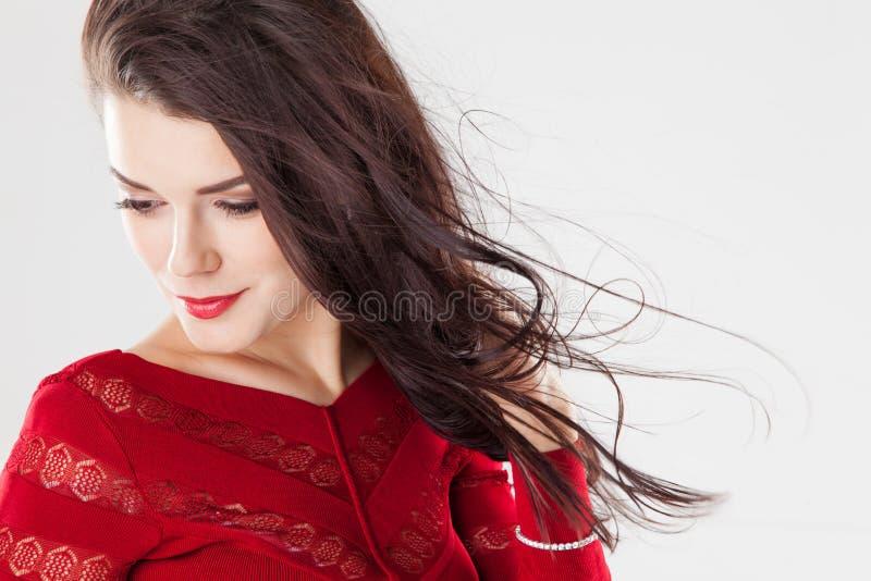 Forme a la mujer morena con el pelo largo que agita en el viento fotografía de archivo