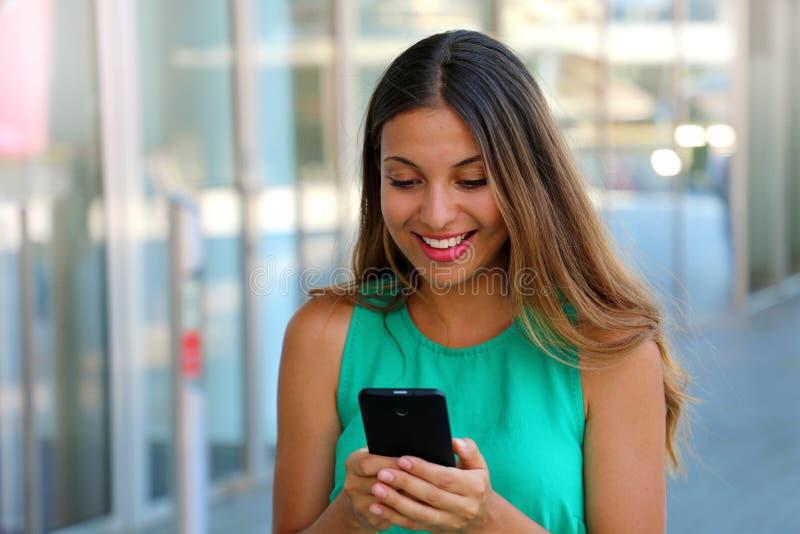 Forme a la mujer que usa el smartphone que se destaca la alameda Mujer joven atractiva que manda un SMS mientras que disfruta de  foto de archivo