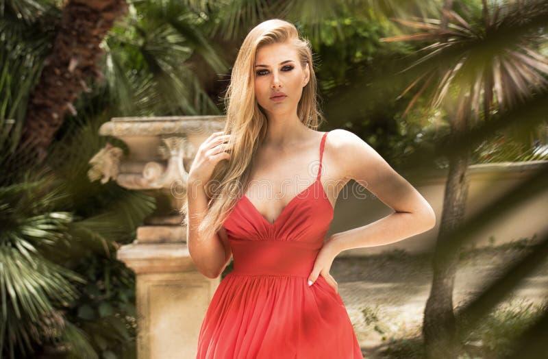 Forme a la mujer rubia en el vestido maxi rojo que presenta en jardín fotos de archivo
