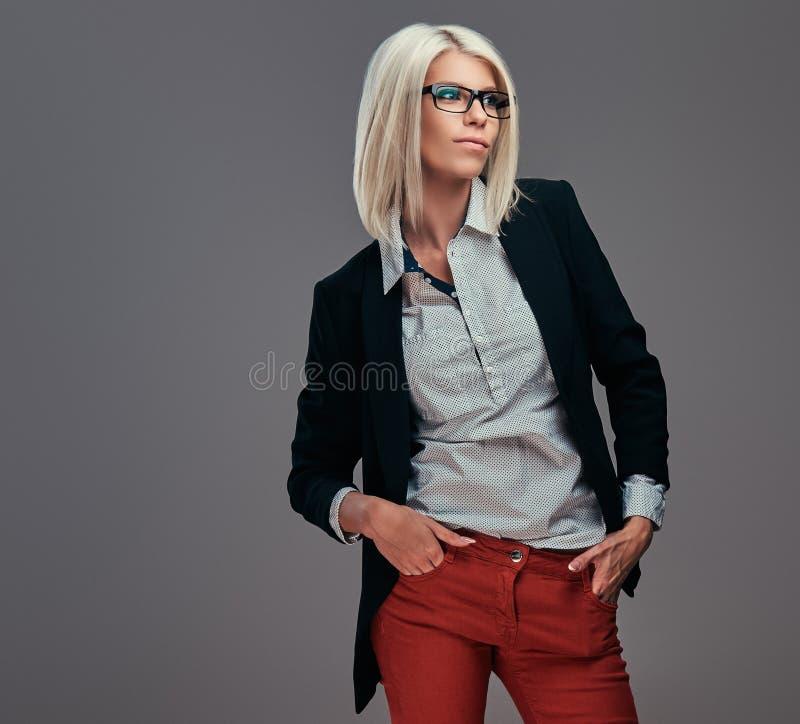 Forme a la mujer rubia en ropa de moda y vidrios que presentan en estudio imagen de archivo libre de regalías