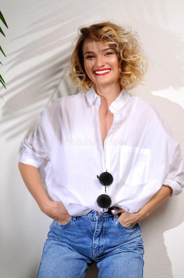 Forme a la mujer rubia sonriente en vaqueros y la camisa blanca fotografía de archivo