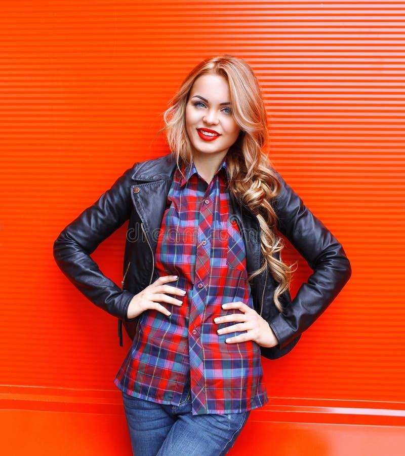 Forme a la mujer sonriente bastante joven que lleva un estilo negro de la roca sobre rojo colorido imagenes de archivo