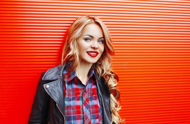 Forme a la mujer sonriente bastante rubia del retrato que lleva estilo negro de la roca sobre rojo colorido foto de archivo