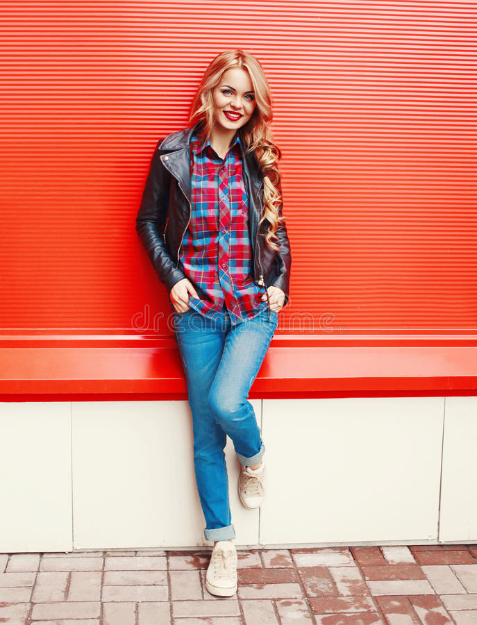 Forme a la mujer sonriente rubia bastante joven que lleva un estilo negro de la roca que presenta sobre rojo colorido imágenes de archivo libres de regalías