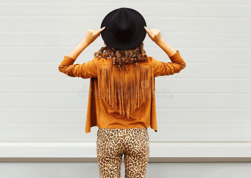 Forme la opinión de la mujer de la parte posterior que lleva un sombrero negro, las gafas de sol y la chaqueta sobre fondo urbano fotos de archivo