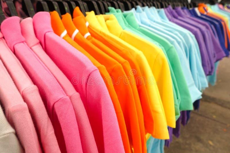 Forme la ropa en el estante de la ropa - armario colorido brillante imagen de archivo libre de regalías
