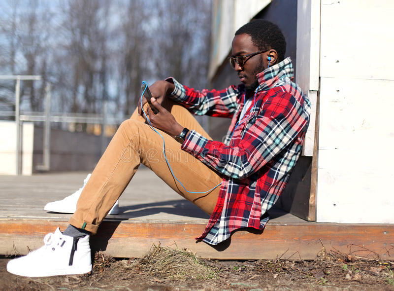 Forme la sentada africana joven del hombre, usando smartphone escucha la música imágenes de archivo libres de regalías