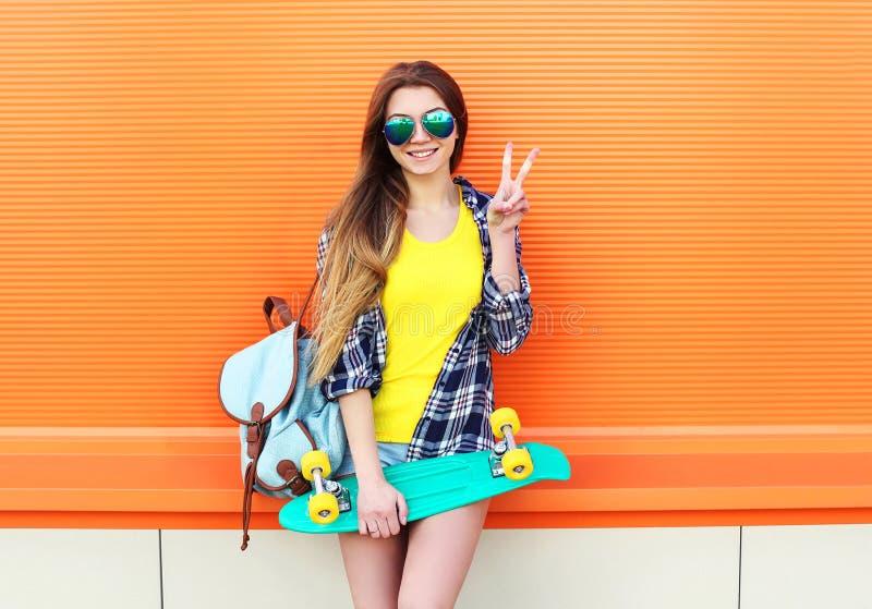 Forme a llevar bastante fresco de la muchacha las gafas de sol, mochila con el monopatín que se divierte imágenes de archivo libres de regalías
