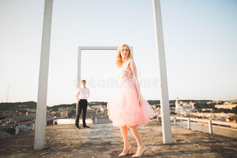 Forme los pares hermosos preciosos que presentan en el tejado con el fondo de la ciudad Hombre joven y al aire libre rubio sensua fotografía de archivo libre de regalías