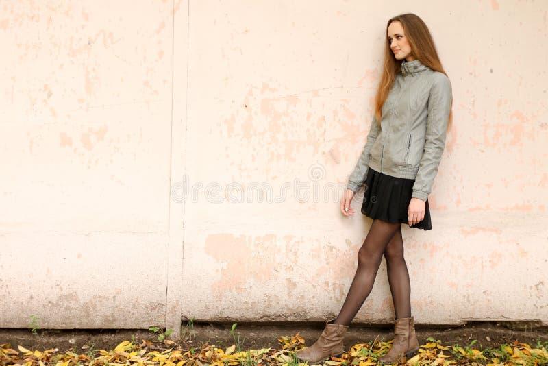 Forme a menina com o cabelo longo que veste a saia preta, o revestimento de trincheira e o casaco de cabedal cinzento imagem de stock