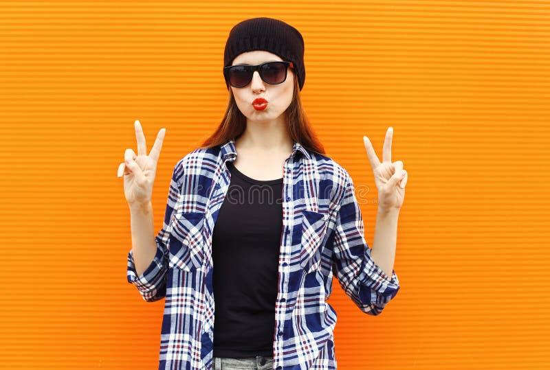 Forme a menina consideravelmente fresca do retrato que veste um chapéu negro, óculos de sol e camisa foto de stock