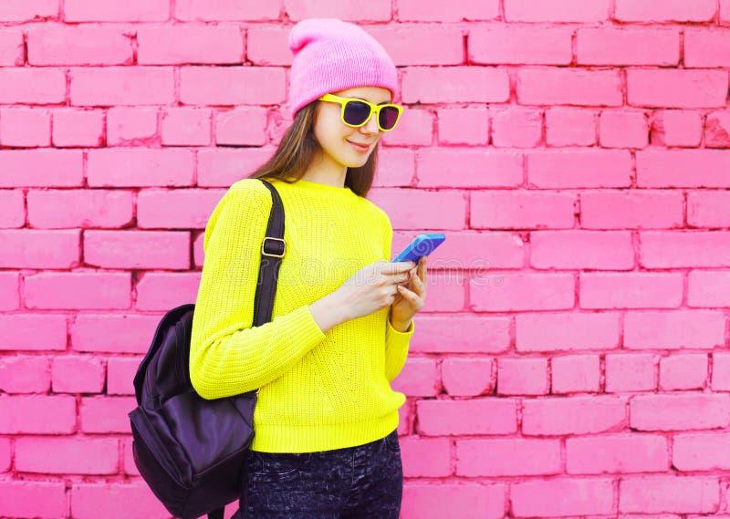 Forme a menina consideravelmente fresca que usa o smartphone sobre o rosa colorido imagens de stock