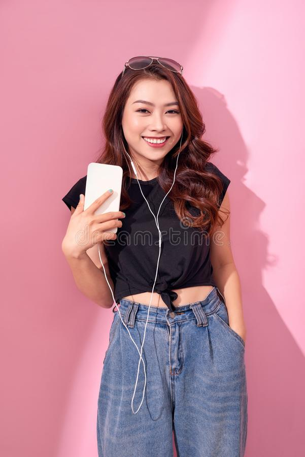 Forme a menina de sorriso consideravelmente fresca, relaxamento, escutando a m?sica com fones de ouvido em um fundo cor-de-rosa imagem de stock royalty free