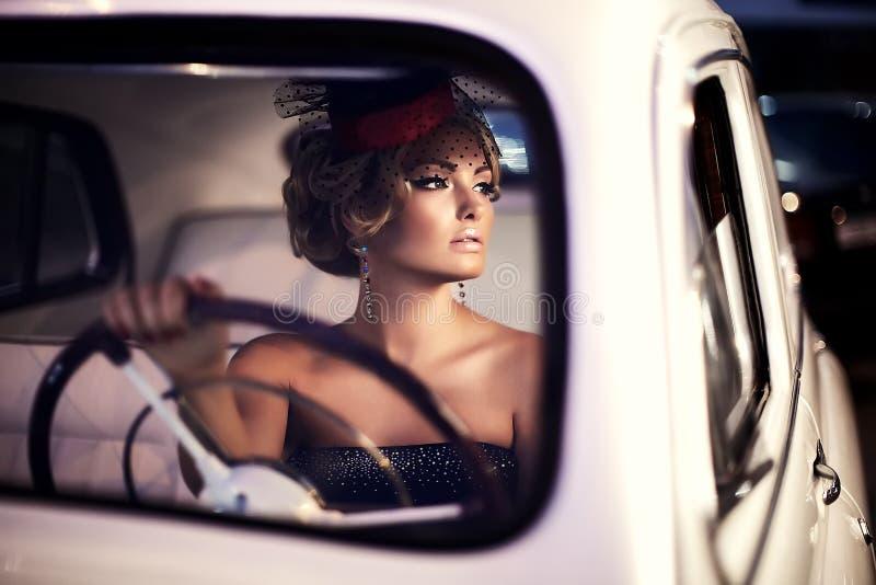 Forme a menina no estilo retro que levanta no carro velho foto de stock