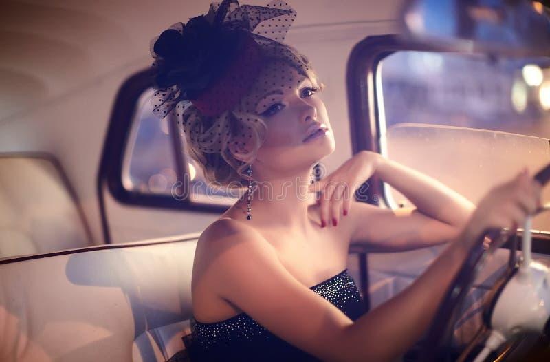Forme a menina no estilo retro que levanta no carro velho fotos de stock