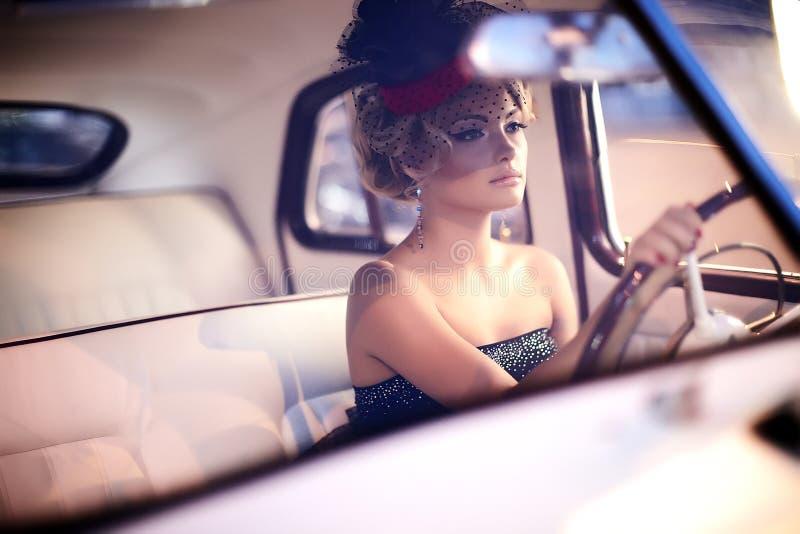 Forme a menina no estilo retro que levanta no carro velho fotografia de stock