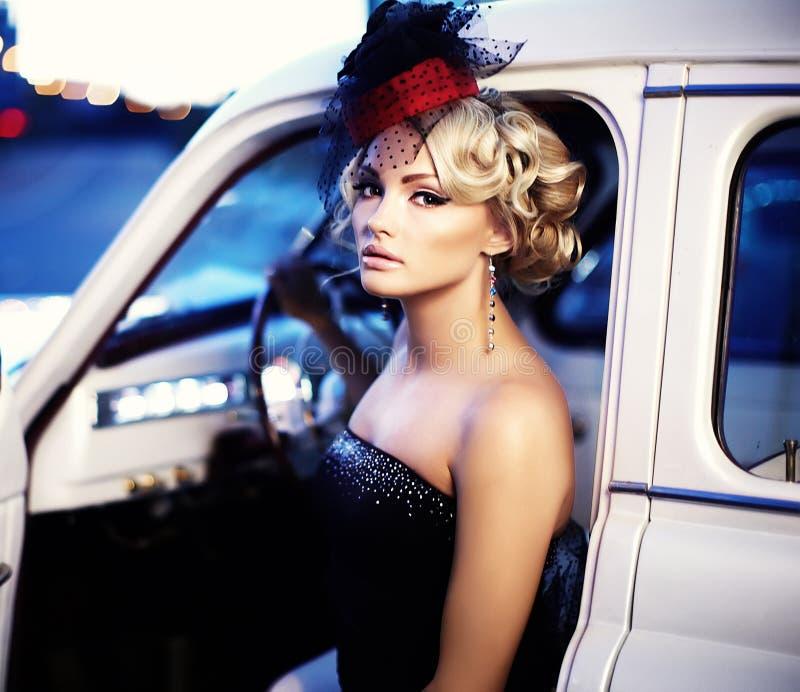 Forme a menina no estilo retro que levanta perto do carro velho imagem de stock