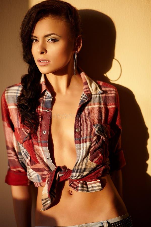 Forme a menina triguenha 'sexy' nas calças de brim e na camisa imagens de stock royalty free