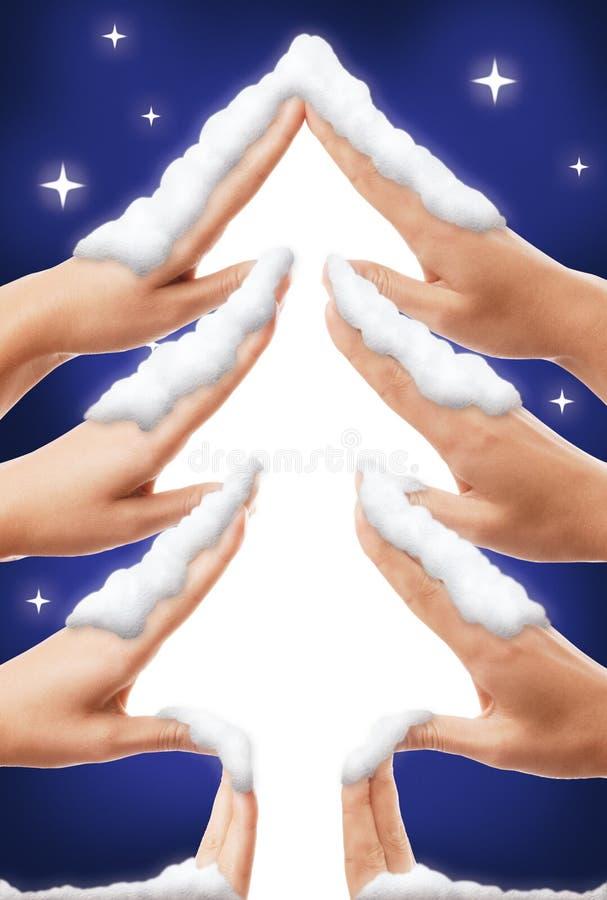 Forme mignonne d'arbre de Noël faite à la main couverts de neige blanche sur le fond étoilé bleu de ciel photos libres de droits