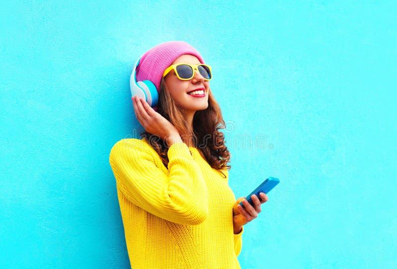 Forme a muchacha despreocupada bastante dulce que escucha la música en auriculares con smartphone las gafas de sol rosadas colori imagen de archivo