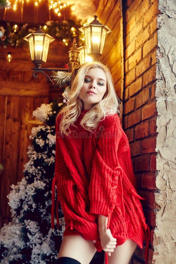 Forme a mujer atractiva el blonde en el suéter rojo, divirtiéndose y presentando contra el árbol de navidad y un invierno del far fotografía de archivo