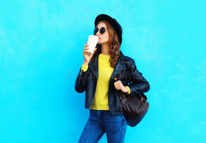 Forme a mujer bastante joven con la taza de café la ropa del negro que lleva de un estilo de la roca sobre azul colorido fotografía de archivo