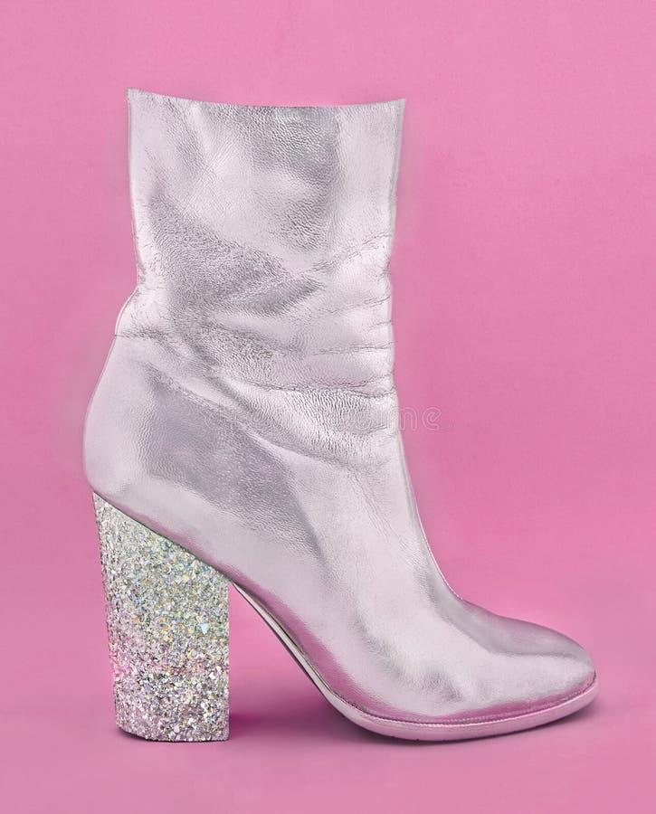 Forme a mujeres de plata brillantes del encanto uno el zapato del ` s con el talón hecho de confeti en fondo de papel rosado Esti fotografía de archivo
