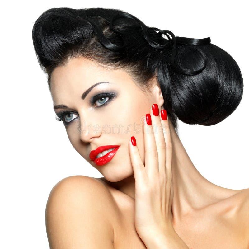 Forme a mulher com bordos vermelhos, pregos e penteado criativo fotografia de stock