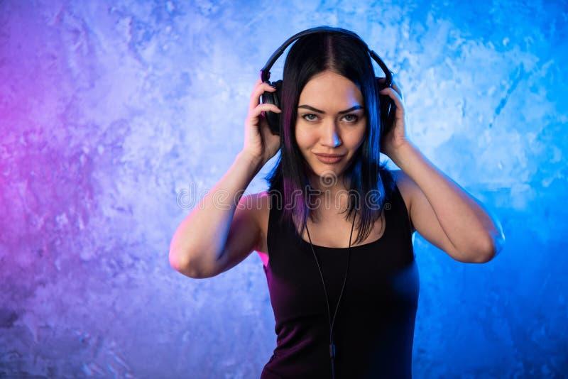 Forme a mulher consideravelmente fresca nos fones de ouvido que escuta a música sobre o rosa e o fundo de néon azul Adolescente n fotografia de stock royalty free