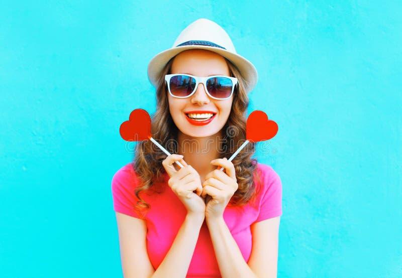Forme a mulher de sorriso feliz com forma do pirulito de dois vermelhos de um coração sobre colorido fotografia de stock