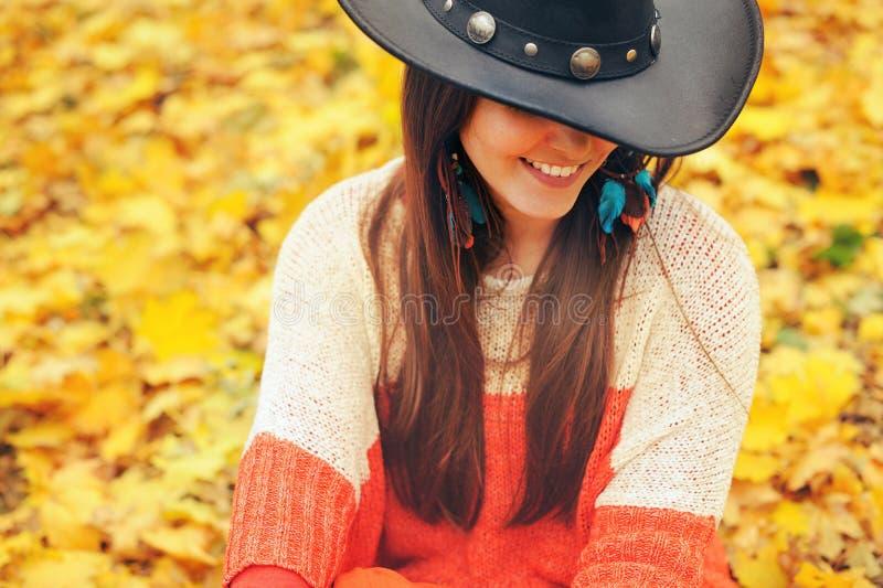 Forme a mulher de sorriso vestida no chapéu chique do estilo do boho, tome um resto no parque do outono imagens de stock royalty free