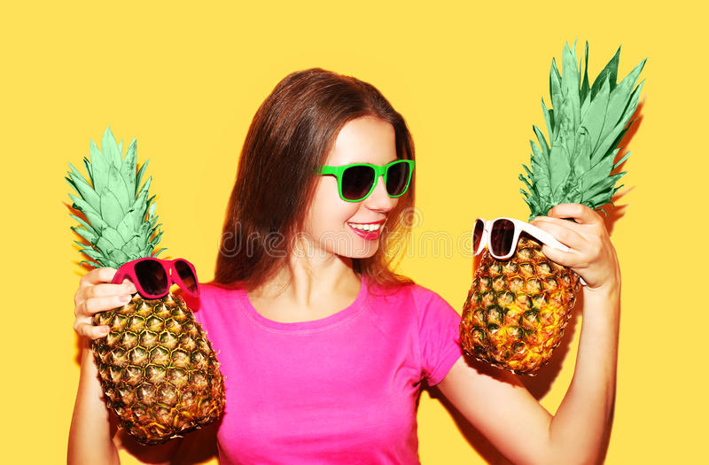Forme a mulher do retrato e o abacaxi dois de sorriso nos óculos de sol foto de stock royalty free