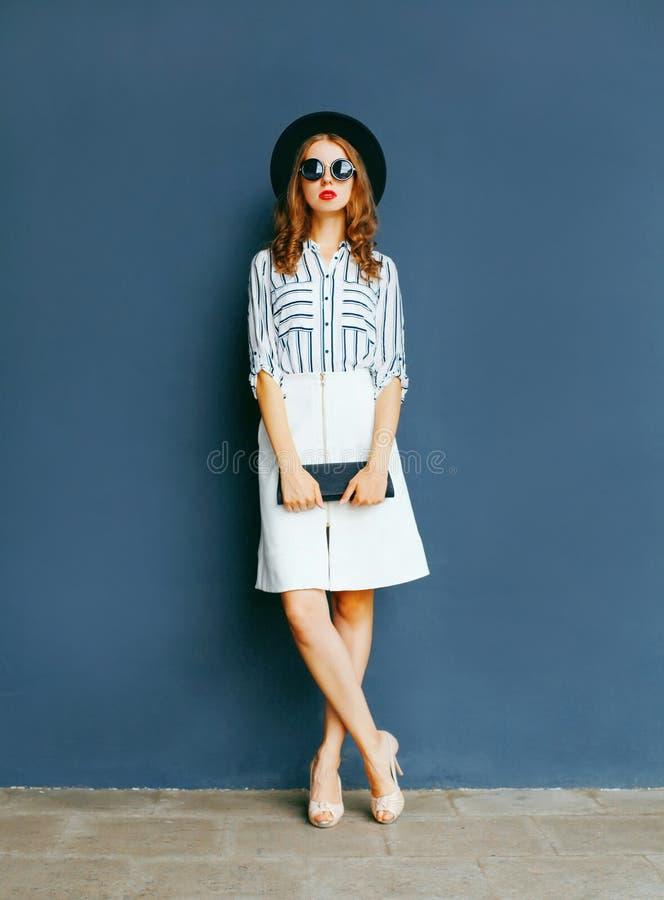 Forme a mulher elegante em um chapéu negro, saia branca com uma bolsa fotografia de stock