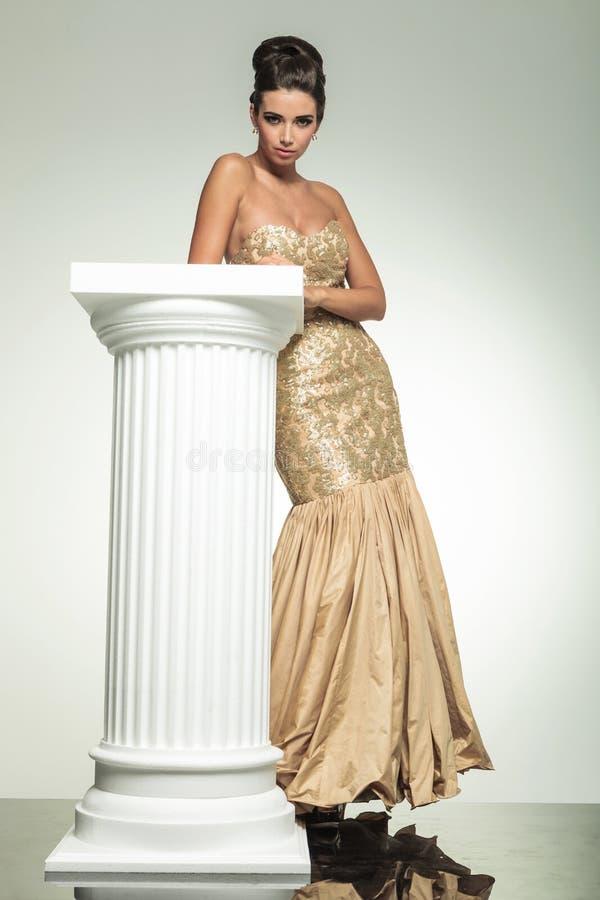 Forme a mulher elegante no vestido dourado que inclina-se em uma coluna imagens de stock royalty free