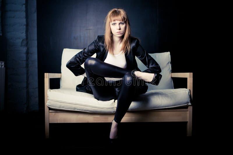Forme a mulher em um sofá em um fundo preto imagem de stock royalty free