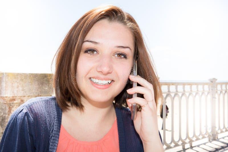 Forme a mulher feliz que usa um telefone esperto em uma rua da cidade imagens de stock