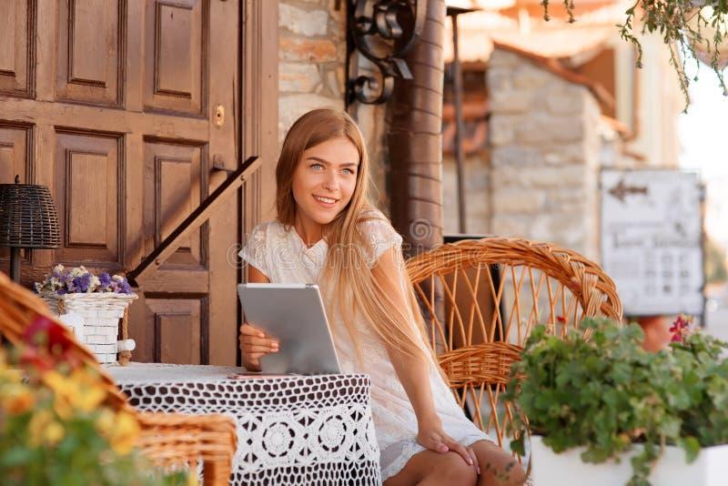 Forme a mulher que usa a tabuleta e sentando-se pela tabela fotos de stock