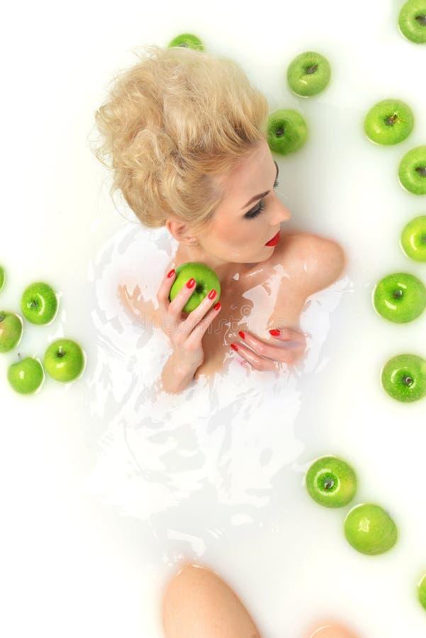 Forme a mulher 'sexy' o relaxamento de encontro dos bordos vermelhos em termas do banho do leite com imagem de stock royalty free